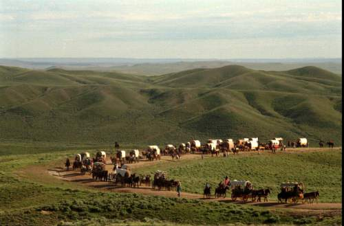 Rick Egan  |  Tribune file photo  A wagon train makes its way up Prospector Hill in Wyoming during a pioneer reenactment in 1997.