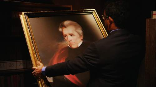 "|  D'Souza Media  Conservative author Dinesh D'Souza holds a painting of Andrew Jackson, in a scene from D'Souza's documentary ""Hillary's America: The Secret History of the Democratic Party."""