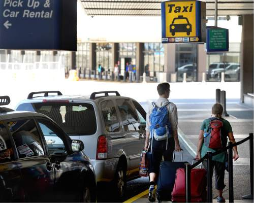 Scott Sommerdorf   |  The Salt Lake Tribune   Travelers walk past the taxi stand at the Salt Lake City International Airport, Wednesday, July 20, 2016.  There have been complaints from airport visitors about largely unregulated taxi fares. Cabs no longer need to have meters, can largely charge any fare they want (except in SLC itself), and need not tell passengers in advance how much they will charge.