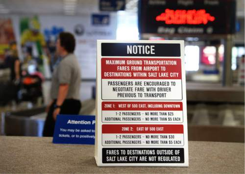 Scott Sommerdorf   |  The Salt Lake Tribune   A sign sits atop the luggage carousel at the Salt Lake City International Airport warning travelers to negotiate their fare with taxi drivers, Wednesday, July 20, 2016.  There have been some complaints of price gouging after deregulation of taxis and ride-hailing companies has created a sort of Wild West atmosphere in the industry.