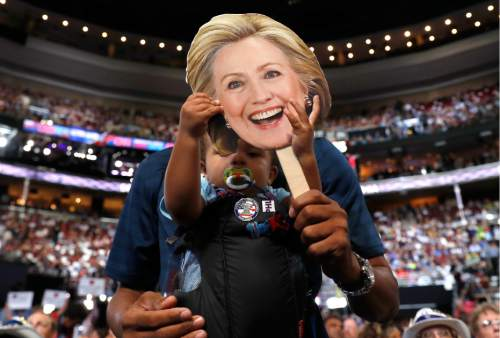 16-month Ethan Jennings grabs a cardboard cutout of the face of Democratic Presidential candidate Hillary Clinton as his father Florida delegate Bernard Jennings holds him during the second day session of the Democratic National Convention in Philadelphia, Tuesday, July 26, 2016. (AP Photo/Carolyn Kaster)