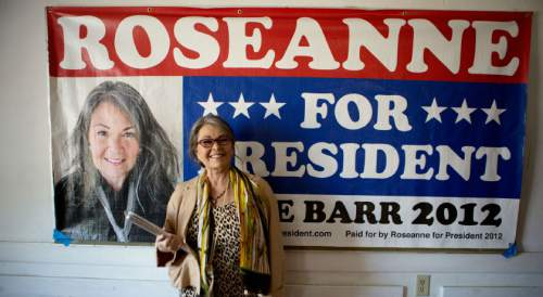 """Roseanne Barr poses with her campaign banner during her 2012 run as a third-party presidential candidate, in a scene from the documentary """"Roseanne For President!"""" Courtesy Sundance Selects/IFC Films"""