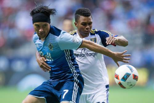 Vancouver Whitecaps' Christian Bolanos, left, and Real Salt Lake's Jordan Allen battle for the ball during the second half of an MLS soccer game on Wednesday July 13, 2016, in Vancouver, British Columbia. (Darryl Dyck/The Canadian Press via AP)