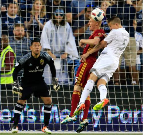 Sporting Kansas City defender Matt Besler (5) tries to head the ball while challenged by Real Salt Lake defender Justen Glad (15) in front of Real Salt Lake goalkeeper Nick Rimando, left, during the first half of an MLS soccer match in Kansas City, Kan., Saturday, May 21, 2016. (AP Photo/Orlin Wagner)