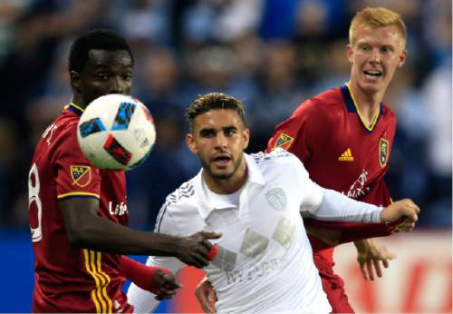 Real Salt Lake midfielder Sunday Stephen, left, and defender Justen Glad, right, watch the ball with Sporting Kansas City forward Dom Dwyer, center, during the first half of an MLS soccer match in Kansas City, Kan., Saturday, April 2, 2016. (AP Photo/Orlin Wagner)
