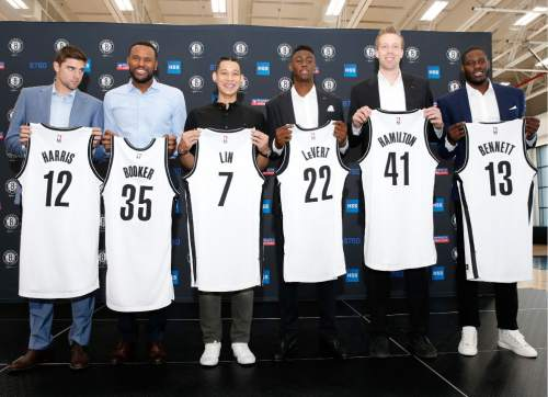 6e809a25e89 Brooklyn Nets new NBA basketball players pose with their jerseys following  a press conference to introduce