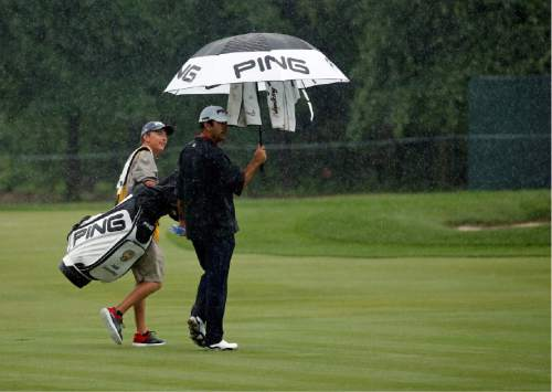 Joe Summerhays, right, and his caddie Caleb Summerhays, left, walk off the course after play was suspended due during the second round of the PGA Championship golf tournament at Baltusrol Golf Club in Springfield, N.J., Friday, July 29, 2016. (AP Photo/Mike Groll)