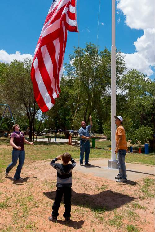 Trent Nelson  |  The Salt Lake Tribune George Jessop raises a flag in Cottonwood Park in Colorado City on Monday July 4, 2016. Jessop, a former member of the FLDS church, is one of those responsible for restarting the community's large gatherings in the park.