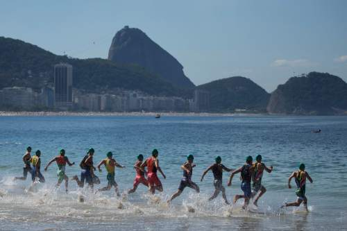 FILE - In this Aug. 2, 2015 file photo, tri-athletes enter the water at the start of the men's triathlon ITU World Olympic Qualification Event on Copacabana beach in Rio de Janeiro, Brazil. Only 50 percent of tickets allocated for Brazilians have been sold. International sales are also reported to be lukewarm. Paralymic sales are much lower. New Sports Minister Ricardo Leyser has promised to boost sales and avoid an embarrassment with television showing banks of empty seats. (AP Photo/Felipe Dana, File)