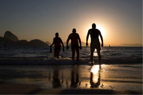 People enter the water for a morning swim at Copabacana beach in Rio de Janeiro, Brazil, Wednesday, July 27, 2016. The iconic Copacabana beach will be the starting point for the road cycling race, marathon swimming and triathlon competitions. (AP Photo/Felipe Dana)