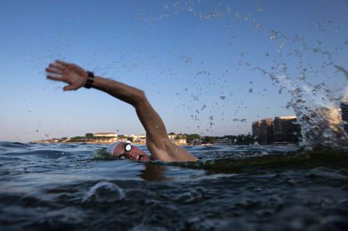 """FILE - In this July 31, 2015, file photo, a triathlete swims in the waters off Copacabana beach during training in Rio de Janeiro, Brazil. The World Health Organization's top water expert said Friday, Aug. 14, 2015, the body """"never advised against viral testing"""" for Rio de Janeiro's polluted waterways where about 1,400 athletes will compete in Olympic events next year. Bruce Gordon, the WHO's coordinator of water, sanitation, hygiene and health, told The Associated Press in a phone interview from Geneva that testing for viruses """"would be advisable"""" given it is known that human sewage pollution is rife in Rio's waters. (AP Photo/Felipe Dana, File)"""