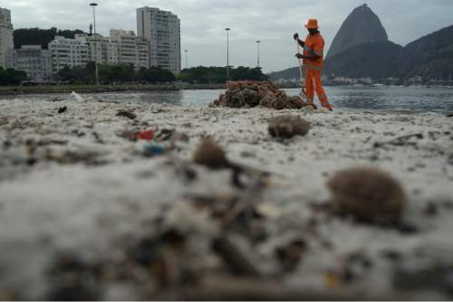 A clean workers removes the trash over the sand of Botafogo beach next to the Sugar Loaf mountain and the Guanabara Bay in Rio de Janeiro, Brazil, Saturday, July 30, 2016. Just days ahead of the Olympic Games the waterways of Rio de Janeiro are as filthy as ever, contaminated with raw human sewage teeming with dangerous viruses and bacteria, according to a 16-month-long study commissioned by The Associated Press.(AP Photo/Leo Correa)