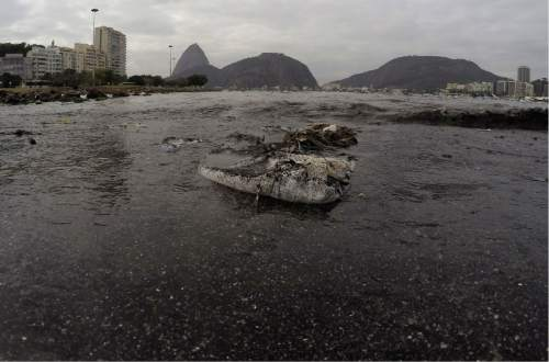 Thrash floats on the water of Botafogo beach next to the Sugar Loaf mountain and the Guanabara Bay where sailing athletes will compete during the 2016 Summer Olympics in Rio de Janeiro, Brazil, Saturday, July 30, 2016. A recent investigation by Associated Press on water quality at aquatic venues for the 2016 Olympic Games in Rio de Janeiro, Brazil, has raised concerns about the risk to the health of athletes who will compete. The games start on August 5.(AP Photo/Leo Correa)