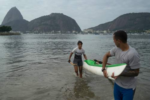 """Sarah Almeida de Freitas, 20, arrives at the Botafogo beach next to the Sugar Loaf mountain and the Guanabara Bay after a practice session in Rio de Janeiro, Brazil, Saturday, July 30, 2016. Freitas, who has been training for 5 year at the bay said.. """"I love my sport but I don't believe the bay will be clean one day. So I take all precautions to avoid any health problems"""".  Just days ahead of the Olympic Games the waterways of Rio de Janeiro are as filthy as ever, contaminated with raw human sewage teeming with dangerous viruses and bacteria, according to a 16-month-long study commissioned by The Associated Press.(AP Photo/Leo Correa)"""