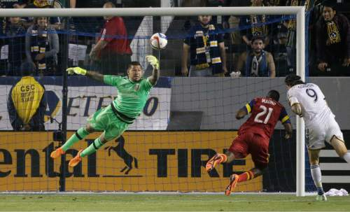 Real Salt Lake goalkeeper Nick Rimando, left, makes a save on a header by Los Angeles Galaxy's Alan Gordon, right, during the second half of an MLS soccer match, Wednesday, May 27, 2015, in Carson, Calif. The Galaxy won 1-0. (AP Photo/Jae C. Hong)