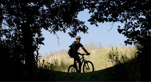 This Wednesday, July 27, 2016, photo, a biker rides along a trail in Salt Lake City. More than 100 million acres of America's most rugged landscapes designated as wilderness are off-limits to mountain bikers, but two U.S. Sens. Mike Lee and Orrin Hatch, both Utah Republicans, have introduced legislation that would allow bikers to join hikers and horseback riders in those scenic, undisturbed areas. The proposal is controversial within the biking community and opposed by conservationists who say bikes would erode trails and upset the five-decade notion of wilderness as primitive spaces. (AP Photo/Rick Bowmer)