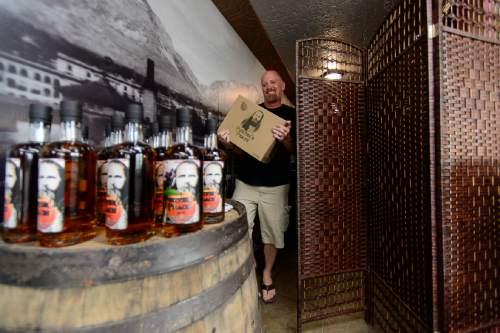 "Trent Nelson  |  The Salt Lake Tribune Co-owner Steve Conlin carries product past a Zion Curtain in front of a tasting station at Ogden's Own Distillery in Ogden, Friday July 15, 2016. Utah distilleries must now have a Zion Curtain, to keep minors from seeing adults taste; distilleries also must offer ""substantial food"" to tasters who may want it."