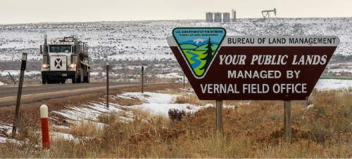 Trent Nelson  |  The Salt Lake Tribune A BLM sign competes with oil wells for attention along the Nine Mile Canyon National Backcountry Byway in Duchesne County, Tuesday January 19, 2016.