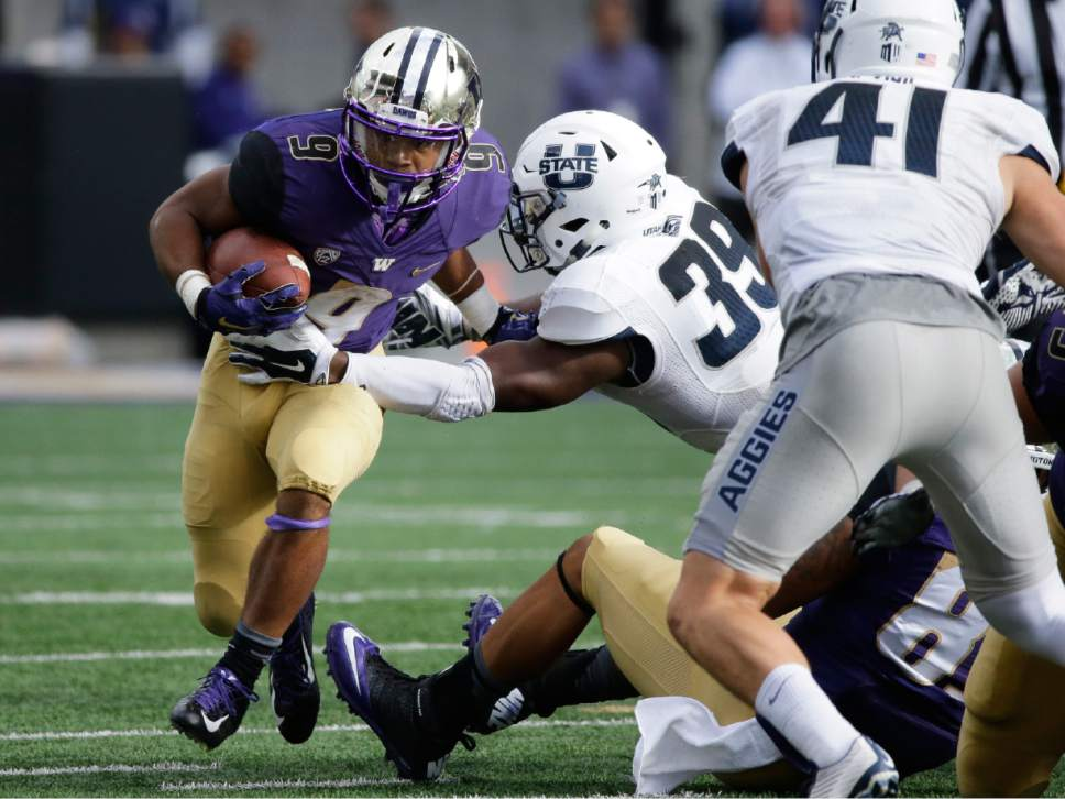Washington's Brandon Beaver, left, carries the ball as Utah State's Torrey Green (39) attempts the tackle in the second half of an NCAA college football game, Saturday, Sept. 19, 2015, in Seattle. Washington won 31-17. (AP Photo/Ted S. Warren)