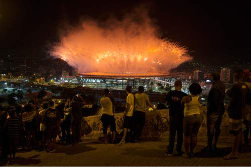 Residents watch fireworks exploding above the Maracana stadium during the opening ceremony of the Rio's 2016 Summer Olympics in Rio de Janeiro in Rio de Janeiro, Brazil, Friday, Aug. 5, 2016. (AP Photo/Leo Correa)