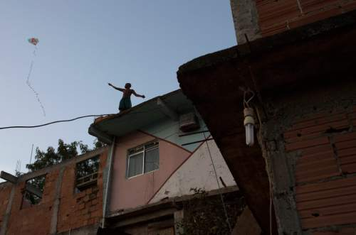 A kid flies his kite from a rooftop in the Mangueira slum next to the Maracana Stadium that will host the Rio's 2016 Summer Olympics open ceremony in Rio de Janeiro, Brazil, Friday, Aug. 5, 2016. (AP Photo/Leo Correa)