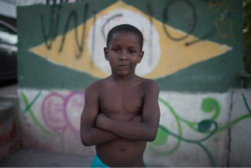 A kid poses for the photo at the Mangueira slum next to the Maracana Stadium that is hosting the Rio's 2016 Summer Olympics opening ceremonies in Rio de Janeiro, Brazil, Friday, Aug. 5, 2016. (AP Photo/Leo Correa)