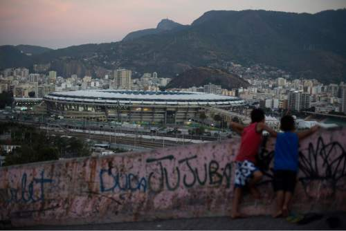Two boys look out from the Mangueira slum towards the Maracana Stadium that is hosting the Rio's 2016 Summer Olympics opening ceremonies, in Rio de Janeiro, Brazil, Friday, Aug. 5, 2016. (AP Photo/Leo Correa)