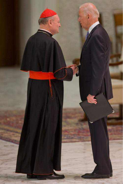 Cardinal Gianfranco Ravasi shakes hands with US vice president Joe Biden as he takes part at a congress on the progress of regenerative medicine and its cultural impact, being held in the Pope Paul VI hall at the Vatican,  Friday, April 29, 2016. (AP Photo/Andrew Medichini)