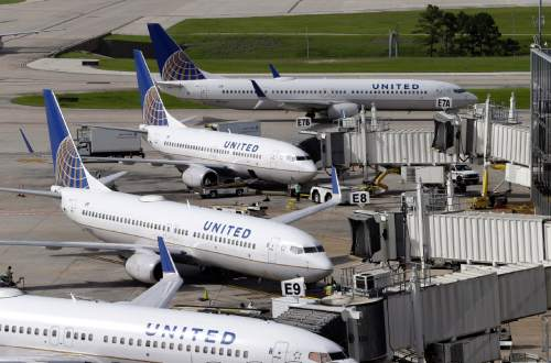 In this July 8, 2015 file photo, United Airlines planes are parked at their gates as another plane, top, taxis past them at George Bush Intercontinental Airport in Houston. (AP Photo/David J. Phillip, File)