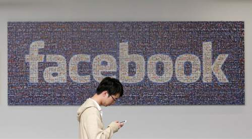 FILE - In this June 11, 2014, file photo, a man walks past a Facebook sign in an office on the Facebook campus in Menlo Park, Calif. Facebook reports financial earnings Wednesday, Jan. 27, 2016. (AP Photo/Jeff Chiu, File)