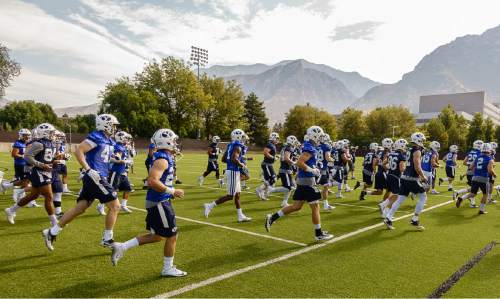 Trent Nelson  |  The Salt Lake Tribune Players warm up at the first BYU fall camp practice under new coach Kalani Sitake, Friday August 5, 2016 in Provo.