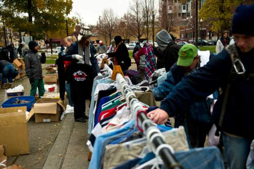 Chris Detrick  |  The Salt Lake Tribune People look at free clothes available for free during The Legacy Initiative Homeless Outreach and Street Boutique at Pioneer Park in Salt Lake City Saturday November 16, 2013.