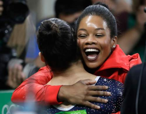 United States' Aly Raisman, back to camera, is embraced by teammate Gabrielle Douglas after her routine on the balance beam during the artistic gymnastics women's team final at the 2016 Summer Olympics in Rio de Janeiro, Brazil, Tuesday, Aug. 9, 2016. (AP Photo/Julio Cortez)