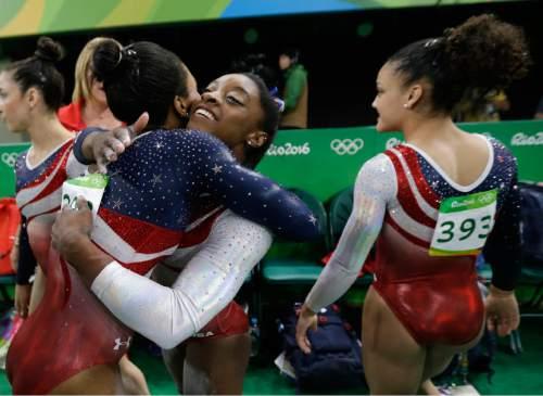 United States' Simone Biles, facing camera, hugs teammate Gabrielle Douglas during the artistic gymnastics women's team final at the 2016 Summer Olympics in Rio de Janeiro, Brazil, Tuesday, Aug. 9, 2016. (AP Photo/Julio Cortez)