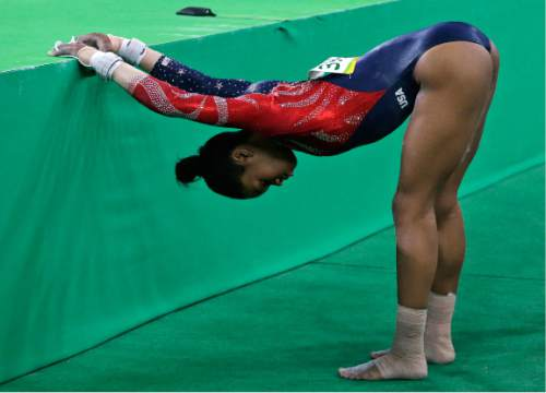 United States' Gabrielle Douglas stretches before her routine on the beam during the artistic gymnastics women's qualification at the 2016 Summer Olympics in Rio de Janeiro, Brazil, Sunday, Aug. 7, 2016. (AP Photo/Rebecca Blackwell)
