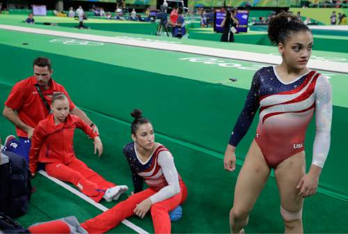 United States' Lauren Hernandez, right, and Aly Raisman rest after their routine on the vault, as teammate Madison Kocian is given a massage during the artistic gymnastics women's team final at the 2016 Summer Olympics in Rio de Janeiro, Brazil, Tuesday, Aug. 9, 2016. (AP Photo/Charlie Riedel)