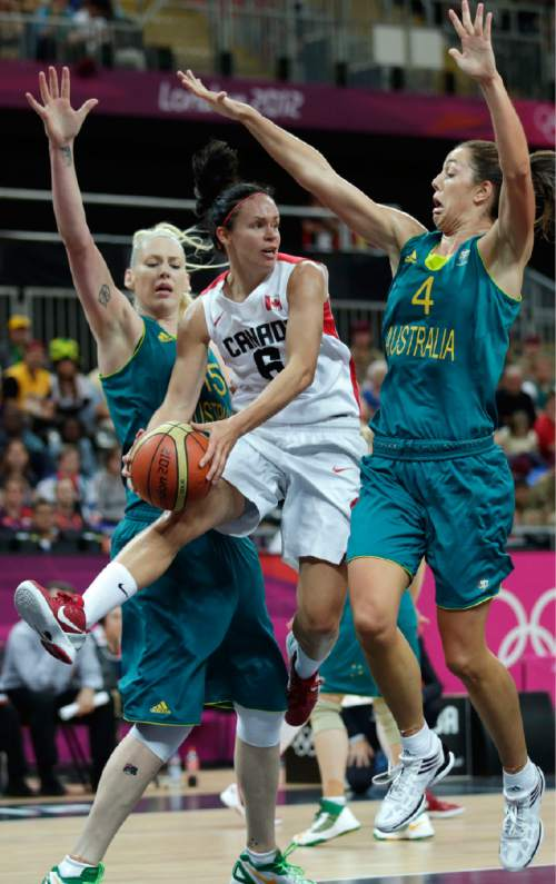 Canada's Shona Thorburn, center, threads between Australia's Jenna O'Hea, right, and Lauren Jackson as she passes the ball during a women's basketball game at the 2012 Summer Olympics, Sunday, Aug. 5, 2012, in London. (AP Photo/Charles Krupa)