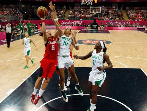 Canada's Shona Thorburn (6) drives against Brazil's Erika Souza (14) and Clarissa Santos (11) during a women's preliminary round basketball game at the 2012 Summer Olympics on Friday, Aug. 3, 2012, in London. (AP Photo/Mike Segar, Pool)