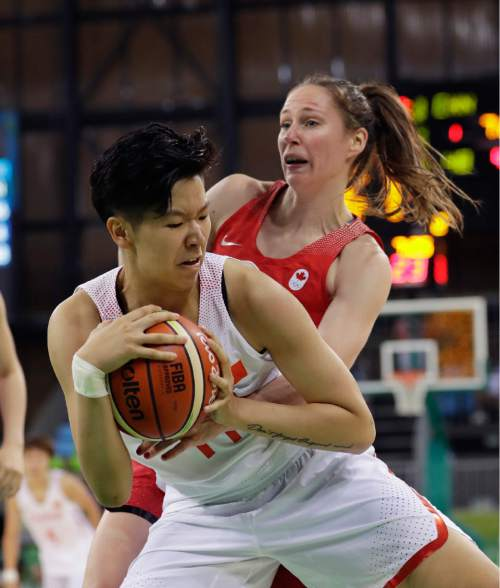 China forward Sijing Huang and Canada guard Kim Gaucher battle for the ball during the second half of a women's basketball game at the Youth Center at the 2016 Summer Olympics in Rio de Janeiro, Brazil, Saturday, Aug. 6, 2016. (AP Photo/Carlos Osorio)