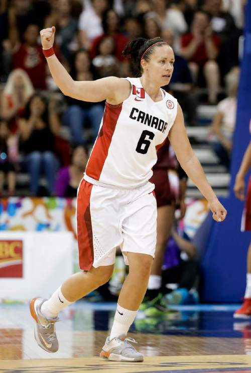 Canada's Shona Thorburn celebrates after hitting a 3-point basket against Venezuela in the first half of a women's preliminary round basketball game at the Pan Am Games Thursday, July 16, 2015, in Toronto. (AP Photo/Mark Humphrey)
