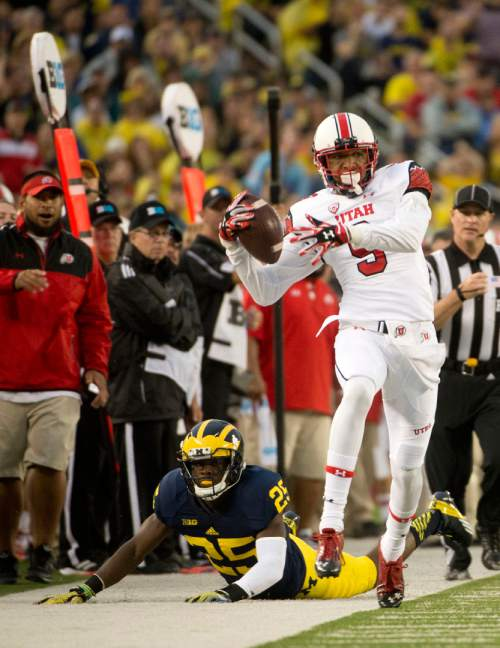 Jeremy Harmon  |  The Salt Lake Tribune  Utah's Tim Patrick (9) is run out of bounds by Michigan's Dymonte Thomas (25) as the Utes face the Wolverines in Ann Arbor, Saturday, Sept. 20, 2014.