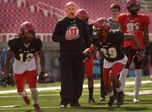 Leah Hogsten  |  The Salt Lake Tribune Guy Holliday, University of Utah football receivers coach, runs through drills with players Saturday, March 26, 2016 at Rice-Eccles Stadium. Holliday, 50, is the only newcomer to Utah's football coaching staff this year and takes over a unit with less proven talent and experience as the Utes lose their top three receiving yard leaders and replace quarterback Travis Wilson.