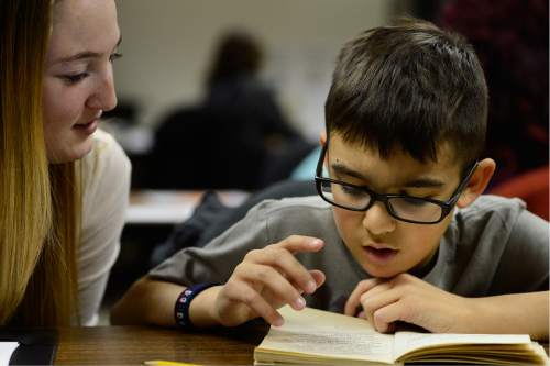 Scott Sommerdorf   |  The Salt Lake Tribune University of Utah student Kailey Stayner listens as  Fourth Grade student Enrique Roman reads at the University of Utah Reading Clinic in Murray. Roman is one of the young students being helped by U of U student tutors, Thursday, February 4, 2016.