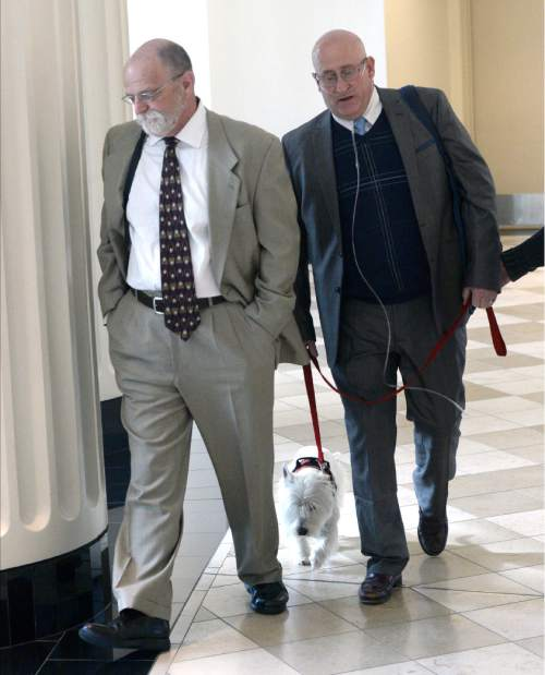 """Al Hartmann     The Salt Lake Tribune Timothy Lawson, right, dubbed a """"fixer"""" for former Utah Attorney General Mark Shurtleff leaves Judge Katie Bernards-Goodman's courtroom in Salt Lake City Monday April 25 with his defense lawyer Ron Yengich and his service dog Prince at his side.  Lawson is charged with six felonies -- including counts of tax evasion, witness tampering, obstruction of justice and a pattern of unlawful conduct -- stemming from allegations that he attempted to intimidate or threaten individuals with ties to Shurtleff and his successor, John Swallow."""