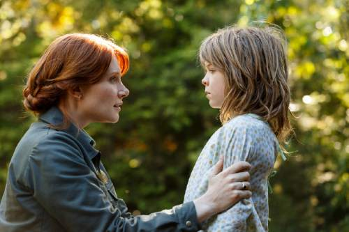"""This image released by Disney shows Bryce Dallas Howard, left, and Oakes Fegley in a scene from """"Pete's Dragon."""" (Matt Klitscher/Disney via AP)"""