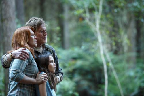 """   Walt Disney Pictures  Grace (Bryce Dallas Howard, left), Meacham (Robert Redford) and Natalie (Oona Laurence) see something amazing in the woods, in a scene from Disney's """"Pete's Dragon."""""""