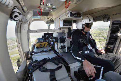 Al Hartmann  photo AirMed flight nurse Brian Simpson on board helicopter at an event with UHP to promote highway safety Thursday May 26.  Stretcher to his left is where critical care patients ride.