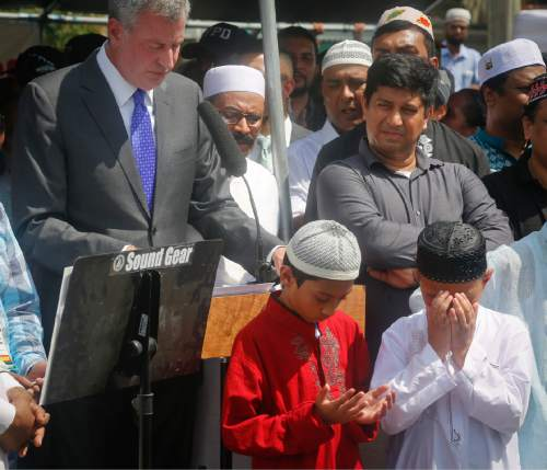 Children of slain Imam Maulama Akonjee stand prayerful in front of New York Mayor Bill de Blasio as he speaks at funeral services for the Imam, Monday Aug. 15, 2016, in New York. Imam Akonjee and Thara Uddin were shot in the head as they left the Al-Furqan Jame Masjid mosque in the Ozone Park section of Queens as they left afternoon prayers Saturday. (AP Photo/Bebeto Matthews)