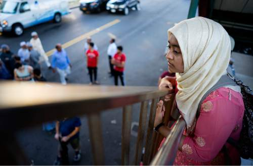 A young woman looks over the area from the steps of an elevated train station Saturday, Aug. 13, 2016, in the Queens borough of New York, near a crime scene after the leader of a New York City mosque and an associate were fatally shot as they left afternoon prayers. Police said 55-year-old Imam Maulama Akonjee and his 64-year-old associate, Tharam Uddin, were shot as they left the Al-Furqan Jame Masjid mosque.  (AP Photo/Craig Ruttle)