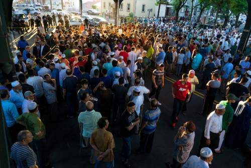 People gather for a demonstration Saturday, Aug. 13, 2016, in the Queens borough of New York, near a crime scene after the leader of a New York City mosque and an associate were fatally shot as they left afternoon prayers. Police said 55-year-old Imam Maulama Akonjee and his 64-year-old associate, Tharam Uddin, were shot as they left the Al-Furqan Jame Masjid mosque.  (AP Photo/Craig Ruttle)
